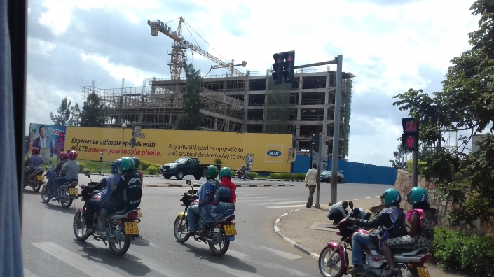Motorcycles move in order, with a construction site in the background